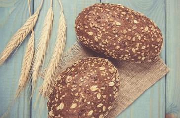 Multi-grain bread rolls on on blue wooden table.