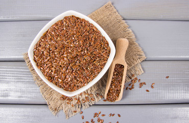 Linseed in a bowl on a wooden background.