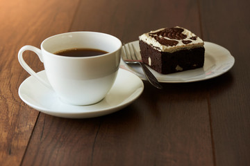 A cup of hot coffee and a piece of chocolate cake