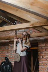Beautiful blonde in glasses and boots standing in attic