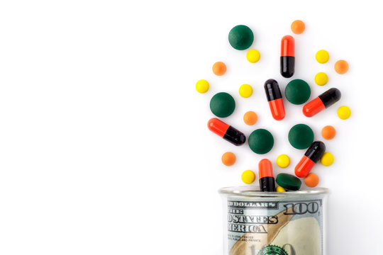 Colorful pills spilled from a bottle made of money, on white background. The Concept of Drug Purchase.