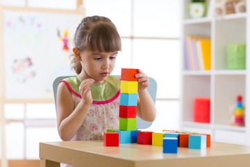 Little child girl plays with wooden colorful cubes