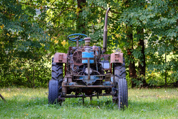 old tractor with rubber tires in green countryside yard in green summer