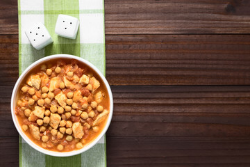 Chicken and chickpea stew or tagine in white bowl, photographed overhead with natural light