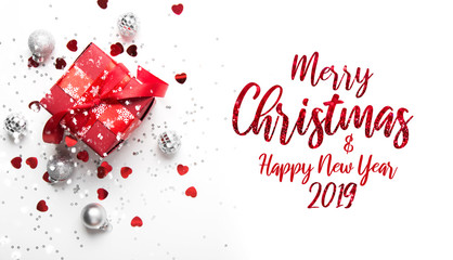 Merry Christmas and Happy Holidays greeting card. New Year. Red gift, present and ornaments on white background top view. Winter holidays.