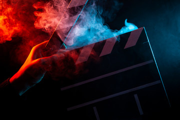 Close-up on an open clapper in hand before starting shooting a film with multi-colored smoke around with red and blue backlighting on a black isolated background