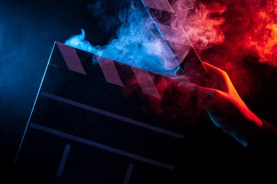 Close-up on an open clapperboard in hand before starting shooting a film with multi-colored smoke around with red and blue backlighting on a black isolated background