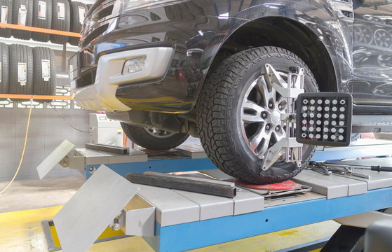 A Car on the Car Steering Wheel Balancer and Calibrate with laser reflector attach on each tire to center driving adjust in the garage