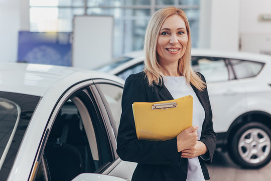 Professional car dealer posing proudly at auto showroom, smiling to the camera, holding clipboard. Happy saleswoman working at automobile dealership, copy space. Professionalism, management concept