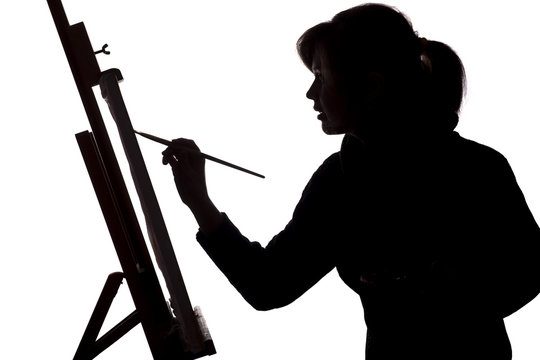 silhouette of a young woman painting on an easel on a white isolated background, the figure of a girl with a brush and gamut, a concept of hobby