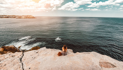 Woman sit on the cliff looking the ocean landscape at sunset.