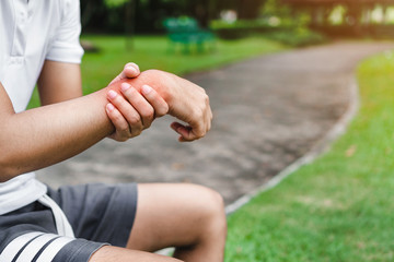 Young man asian have accident and holding him wrist pain twist sprain in sport exercise jogging, selective focus.