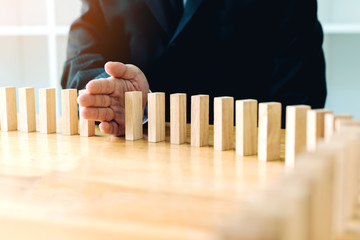 Close up hand businessman stopping wooden block from falling in the line of domino with risk concept.