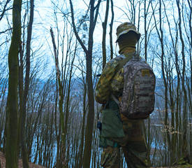 Rear view of military young man with backpack on cold dark forest background.