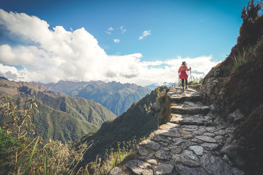 A female hiker is walking on the famous Inca trail of Peru with walking sticks. She is on the way to Machu Picchu.