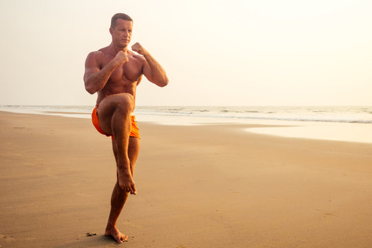Attractive bare chested man during workout at a beach. sporty male model doing fitness workout at a beach on a sunny sunset evening.