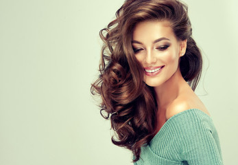 Beautiful model girl with long wavy and shiny hair . Brunette woman with curly hairstyle   Wall mural