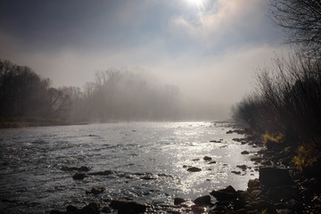 Morning sun and fog hovering over a mountain river.