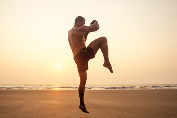 Strong boxer shirtless coach during kickboxing exercise with trainer in boxing gloves at sunset.sports figure, perfect abdominal muscles motivation