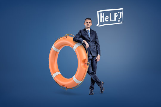 A businessman stands leaning on a large orange life buoy with a speech bubble holding a word Help inside.