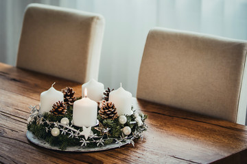 Advent Wreath with four candles. The first candle being lit on the first Sunday in December to celebrate the beginiing of Christmas holidays in Switzerland. Warm darker tones, wooden table background.