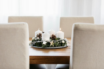 Lighting the first candle on the Advent Wreath on the first Sunday in December to celebrate the beginiing of Christmas holidays in Switzerland. Dining table decoration.
