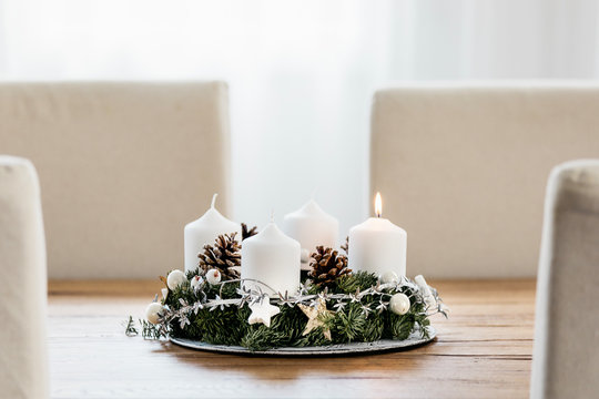 Close up of Advent Wreath with four candles. The first candle being lit on the first Sunday in December to celebrate the beginiing of Christmas holidays in Switzerland. Dining table decoration.