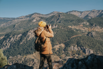 Nature Photographer taking pictures outdoors during hiking trip.