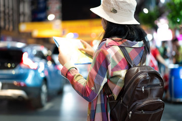 Asian traveler or tourist is looking at the map to find the way to go for traveling at night time.
