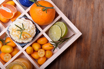 Cupcake garnished with butter cream, citrus curd, kumquats, mandarins, lime and Christmas balls in a wooden box with cells