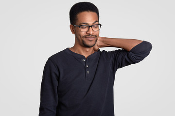 Photo of displeased dark skinned man keeps hand on nek, looks aside, closes eyes, feels fatigue and sleepy, wears optical glasses for good vision, isolated over white background. Afro American male