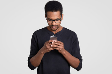 Photo of concentrated dark skinned handsome guy reads news in internet, holds cell phone, wears transparent glasses and sweater, isolated over white background, checks email box, uses free internet