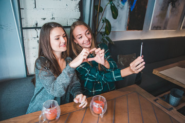 two girlfriends taking selfie while sitting in cafe