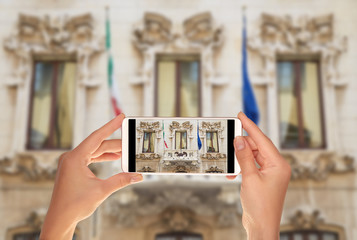 A tourist is taking a photo of of the old house in Milan with flags of the European Union and Italian on a mobile phone