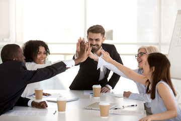 Happy motivated diverse business team people giving high five together celebrating goal achievement, team spirit, coaching engaging in corporate success, unity, good relations work result, reward