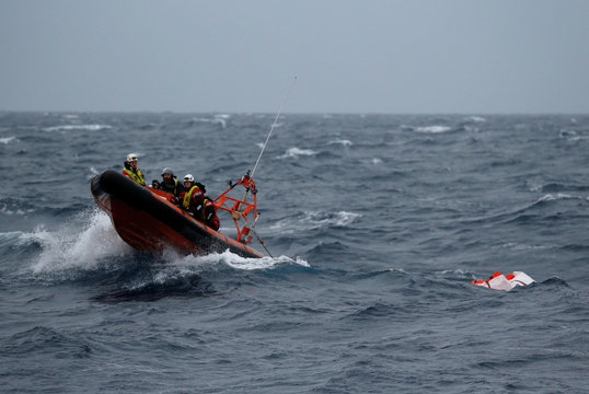 A rigid-hulled inflatable boat (RHIB) from the migrant search and rescue ship Sea-Watch 3 tows a raft carrying life jackets during a training exercise in the central Mediterranean