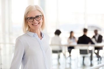 Smiling mature attractive businesswoman in glasses looking in camera, happy friendly middle aged female executive, older team leader or business coach mentor posing in office, headshot portrait