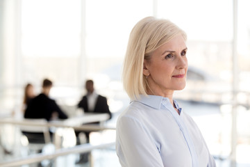 Thoughtful dreamy middle aged businesswoman looking away thinking of new goals opportunities in office, serious mature senior old woman planning future, dreaming of success, business vision concept