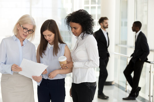 Mature team leader and young female employees discussing paperwork standing in office, diverse employees talking about document, executive giving instructions explaining work to colleagues interns