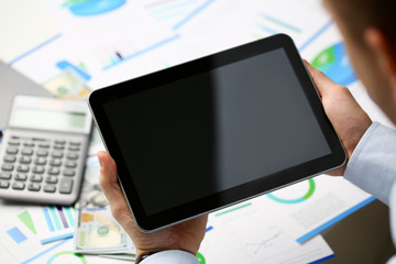 Businessman holds tablet on background