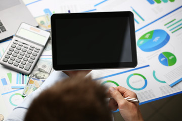 Businessman holds tablet on background