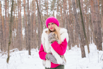 Beauty, fashion, people concept - attractive blond woman walking in pink hat and sweaters in winter wood