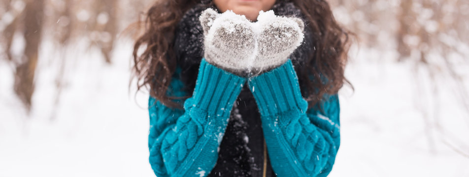 Close up of christmas Girl. Winter young woman blowing snow in winter nature
