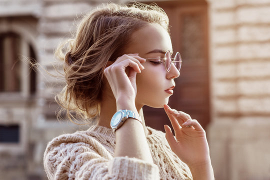 Outdoor close up portrait of young beautiful fashionable girl wearing purple sunglasses, sweater, wrist watch, posing in street of european city. Copy, empty space for text