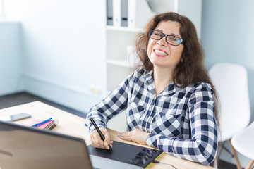 Photography, web design and graphic art concept - woman in glasses using mouse pan sketch device. Photo camera on the desk in coworking space