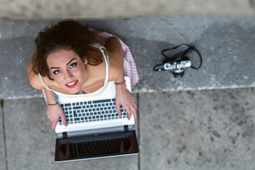 Woman sitting outside on stairs and using laptop