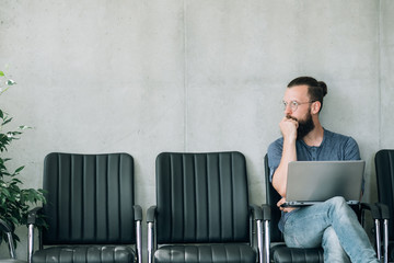 pensive man waiting for his job interview. thoughtful guy sitting on the chair.