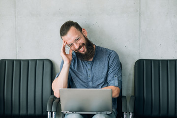 funny videos and idle leisure concept. man laughs watching entertaining website on laptop