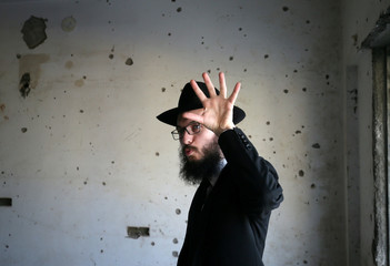 Rabbi Israel Kozlovsky gestures next to a wall riddled with bullet holes after the renaming of Nariman House as Nariman Light House, which was one of the targets of the November 26, 2008 attacks, in Mumbai