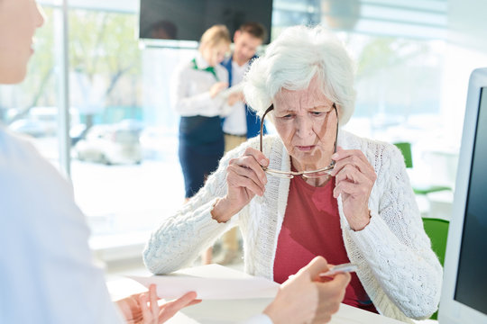 Serious confused senior lady with gray hair sitting at table and looking through eyeglasses while examining document shown by manager in bank office